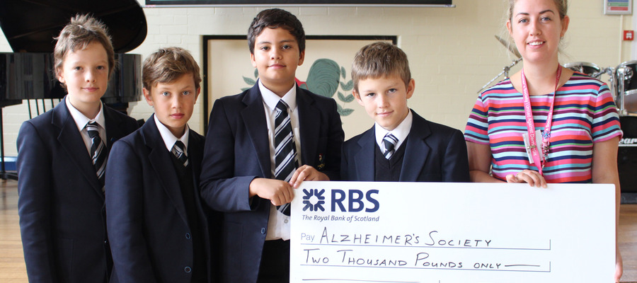 Bolton School Junior Boys present a cheque for £2000 to Alzheimer's Society's Stephanie Potts, Community Fundraiser for Greater Manchester