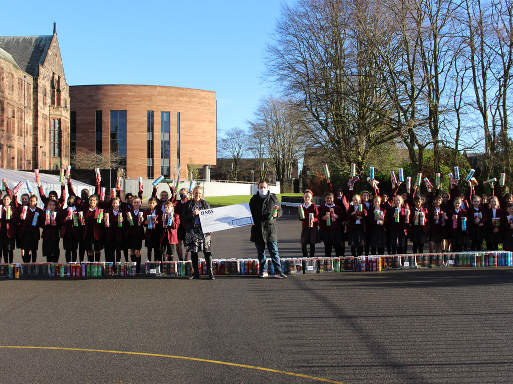 Senior Girls and Junior Girls handing over the cheque and Pringles to Urban Outreach on behalf of Bolton School