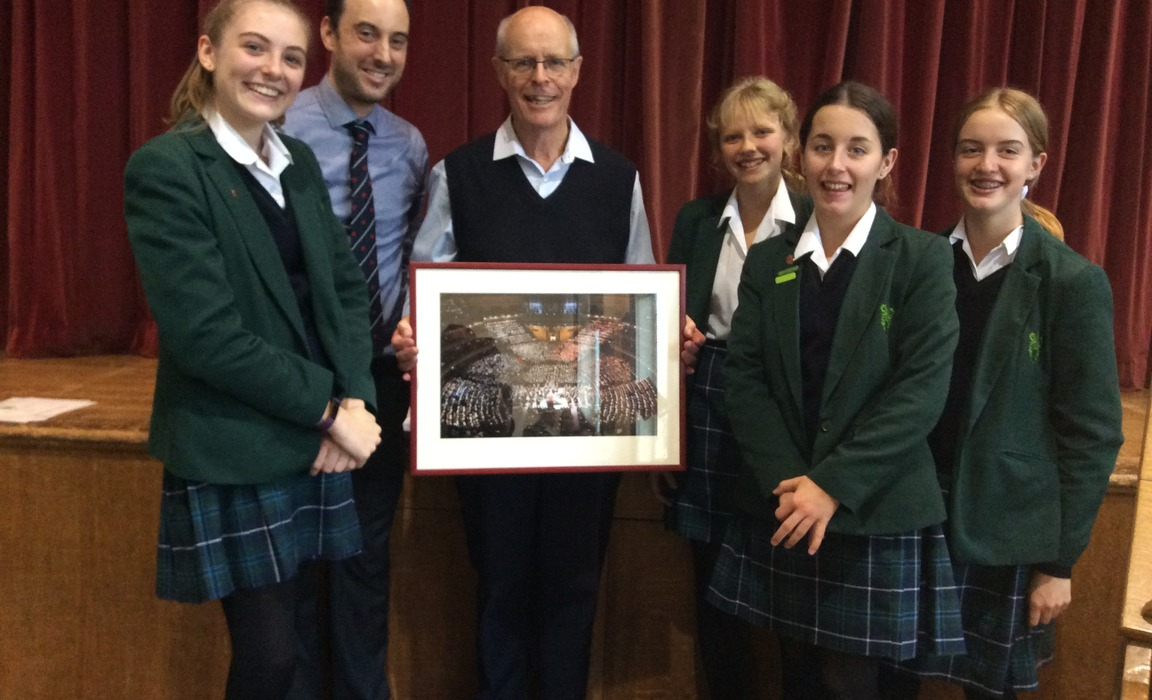 Brian Kay (centre holding photo) with Matt Dury, Director of Music at Bruton School for Girls and members of the school choir.