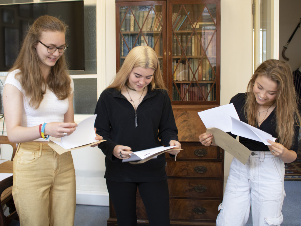 Georgia and twins, Madeleine and Faye, open their results. From left: Georgia Hughes with twins Madeleine and Faye Lynch-Williams