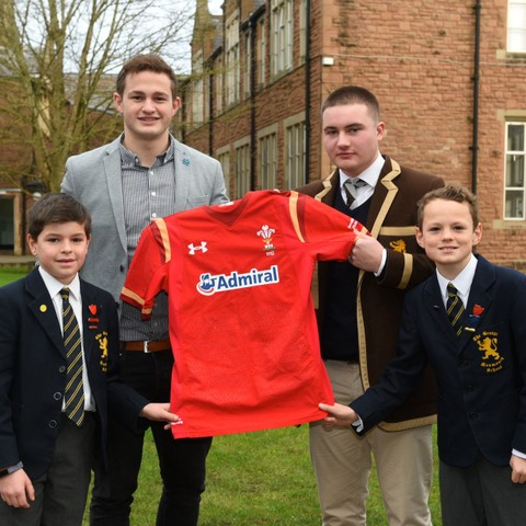 Rugby ace Hallam Amos presents a Wales jersey to Monmouth School for Boys' Captain of Rugby, Alexi Webb, flanked by promising players from Monmouth Sc
