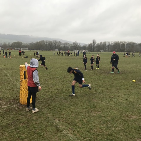 Former solider Darren Carew, wearing the red cap, coaches a rugby session for Monmouth pupils.