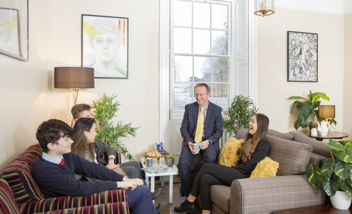 Head of College in the Sitting Room with students