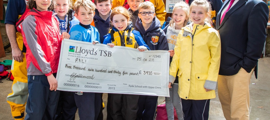 Headmaster Mark Waldron, together with pupils of Ryde Junior School, presenting a cheque to members of Bembridge RNLI