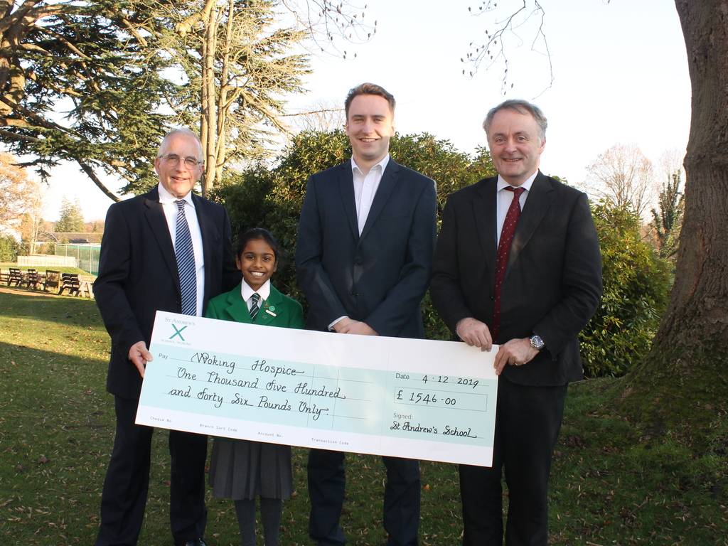 Current pupil, alumnus Mr Kyle Jackson together with Headmaster Mr Adrian Perks present the cheque to Mr Tim Stokes, Chair of Woking Hospice (left)