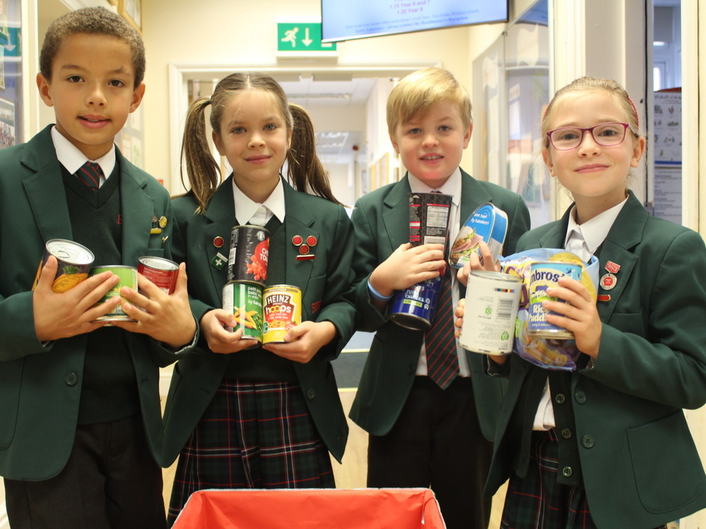 Pictured are Bede's Prep pupils with some of the items of food collected for the School's Harvest Festival
