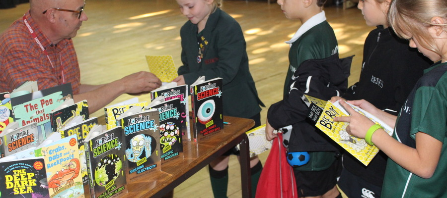 Tony De Saulles signing books for the children at Bede's Prep