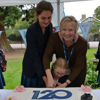 Headmistress Charlotte Avery cuts celebration cake with 2 students.
