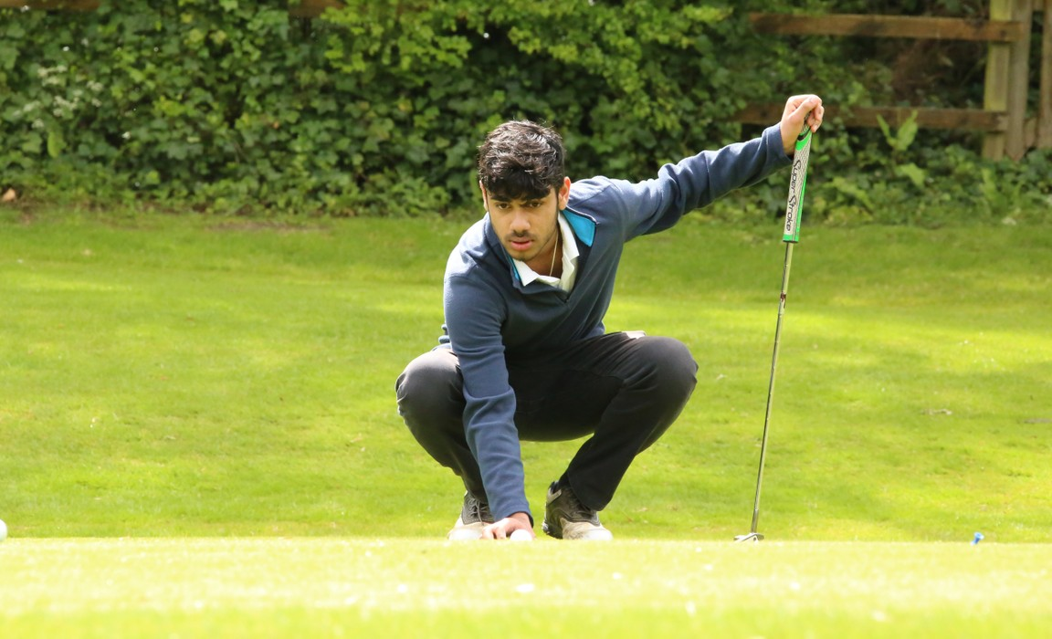 Tanay Shah lines up a putt on the green